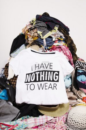 Photo for Close up on a untidy cluttered wardrobe with colorful clothes and accessories, many clothes and nothing to wear. - Royalty Free Image