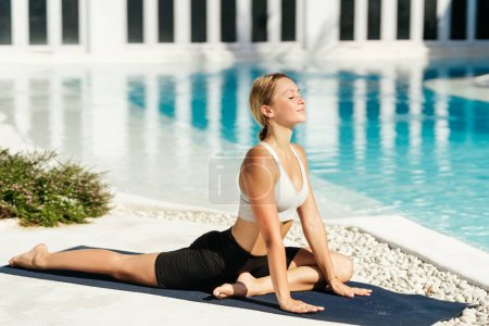 Photo for Woman doing stretching exercises outdoors in the morning. Beautiful happy sport fitness model outside on summer spring day. - Royalty Free Image