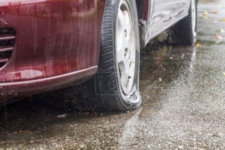 Car flat tire in rainy day