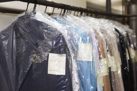 Photo for Dry cleaning things hanging in a row on a hanger - Royalty Free Image