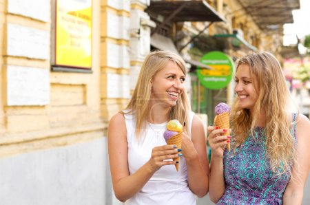Photo for Two female friends having fun and eating ice cream - Royalty Free Image