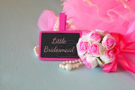 Small girls party outfit: crown and wand flowers next to small chalkboard with phrase LITTLE BRIDESMADE: on wooden table. bridesmaid or fairy costume. glitter overlay. selective focus