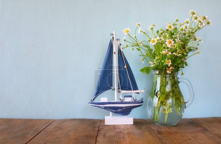 fresh daisy flowers next to wooden boat on wooden table