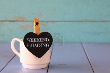Photo for Cup of coffee and little heart shape chalkboard with the phrase: WEEKEND LOADING. - Royalty Free Image