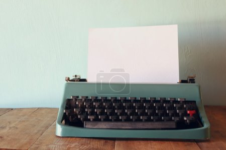Photo of vintage typewriter with blank page on woo...