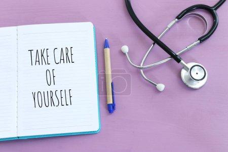 concepto de autocuidado. cuaderno con texto sobre fondo púrpura pastel
