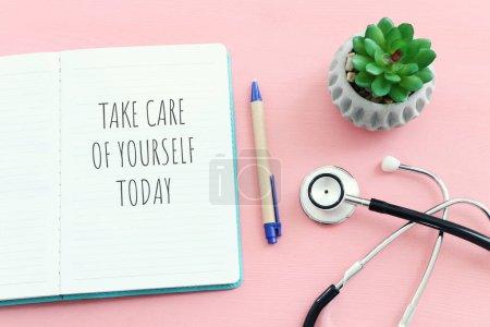 concepto de autocuidado. cuaderno con texto sobre fondo rosa pastel