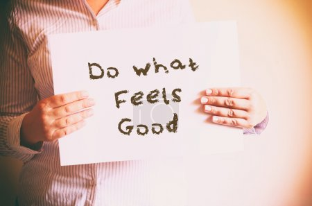 """Woman holding board with the phrase """"do what feels good"""" written on it"""