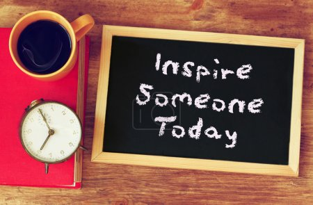 Photo for Black board with the phrase inspire someone today written on it. over wooden table with coffee and vintage clock - Royalty Free Image