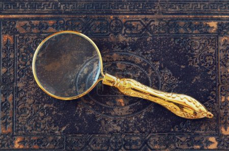 Photo for Macro image of magnifying glass over antique black cover - Royalty Free Image