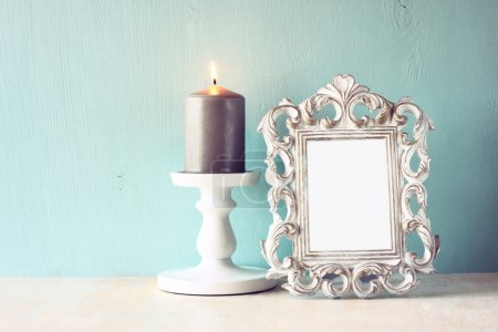Low key image of vintage antique classical frame and Burning candle on wooden table. filtered image