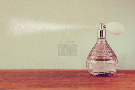Photo pour Bouteille de parfum Vintage antiques avec effet de parfum en atomiseur, sur une table en bois. image filtrée rétro - image libre de droit