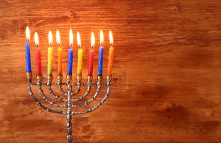 Low key image of jewish holiday Hanukkah background with menorah Burning candles over wooden background