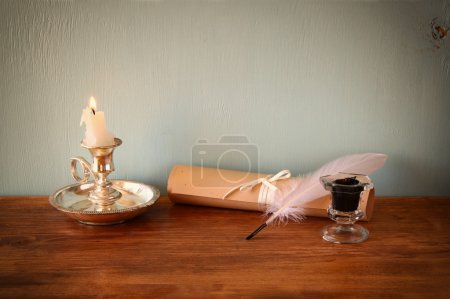 Low key image of white Feather, inkwell and scroll on old wooden table