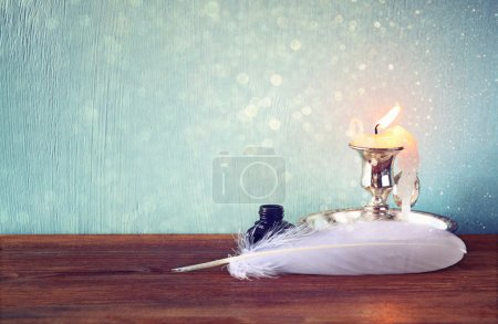 Low key image of white Feather, inkwell, scroll and candle and  glitter lights background on old wooden table