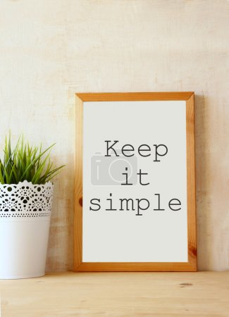"""Photo for White drawing board with the phrase """" keep it simple"""" written on it against textured wall - Royalty Free Image"""