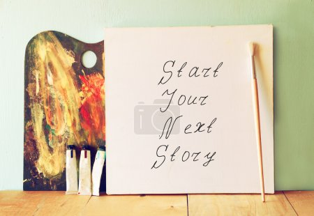 Canvas with the phrase start your next story next to oil paints and palette