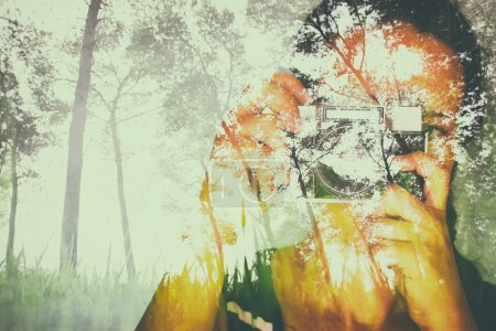 Double exposure image of young girl holding old camera and nature background