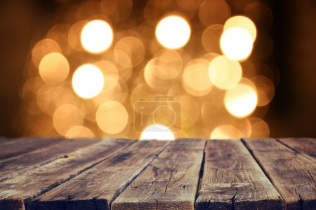 Photo for Rustic wood table in front of glitter gold bright bokeh lights - Royalty Free Image