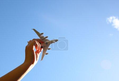 Photo pour Photo rapprochée de la main de la femme tenant un avion jouet contre le ciel bleu avec des nuages - image libre de droit