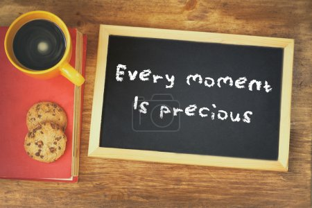 Top view of blackboard with the phrase every moment is precious next to coffee cup over wooden table