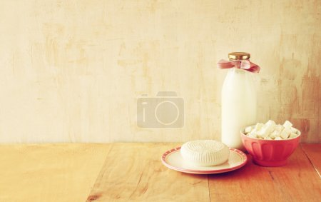 Greek cheese , bulgarian cheese and milk on wooden table over rustic background. Symbols of jewish holiday - Shavuot
