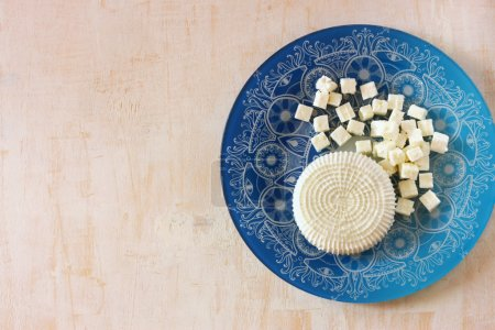 Top view of greek cheese and bulgarian cheese on wooden table over wooden textured background. Symbols of jewish holiday - Shavuot