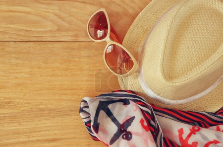Top view of stylish hat woman sunglasses and tablet fashion nautical scarf over wooden table. vacation and travel concept
