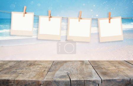 Photo pour Ancien polaroid photo frames hnaging sur une corde avec fond de plage - image libre de droit