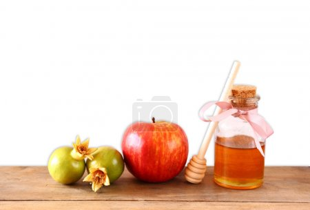 rosh hashanah (jewesh holiday) concept - honey, apple and pomegranate over wooden table with white isolated background. traditional holiday symbols.