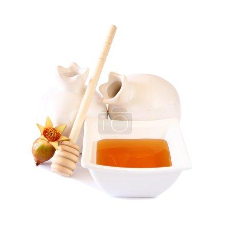 rosh hashanah (jewesh holiday) concept - honey and pomegranate isolated on white. traditional holiday symbols.