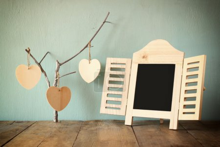 decorative chalkboard frame and wooden hanging hearts over wooden table. ready for text or mockup