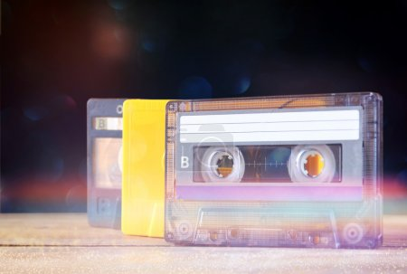 Stack Cassette tapes over wooden table. retro filtered with glitter overlay