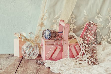 vintage jewelelry, antique wooden jewelry box  and perfume bottle on wooden table. filtered image