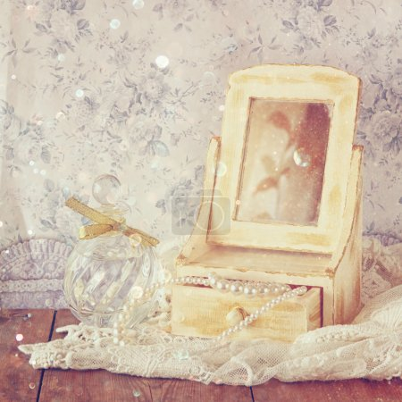 vintage pearls , antique wooden jewelry box with mirror and perfume bottle on wooden table. filtered image