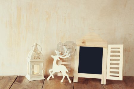 abstract filtered photo of decorative chalkboard frame and wooden deer over wooden table. ready for text or mockup.