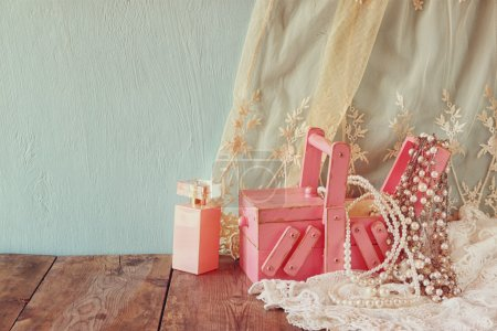 vintage jewelery, antique wooden jewelry box and perfume bottle on wooden table. filtered image