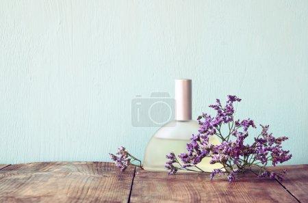 Photo pour Bouteille de parfum vintage fraîches à côté de fleurs aromatiques sur table en bois. image filtrée rétro - image libre de droit
