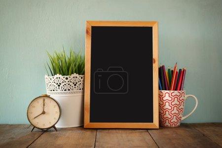 Photo pour Tableau noir, pile de crayons colorés et horloge. concept de retour à l'école - image libre de droit