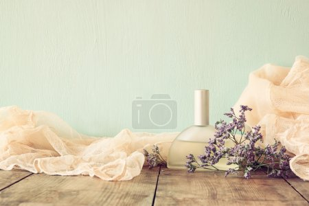 Photo for Fresh vintage perfume bottle next to aromatic flowers on wooden table. retro filtered image - Royalty Free Image