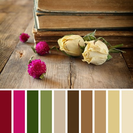 Selective focus image of dry rose and old vintage books on wooden table. vintage filter with palette color swatches
