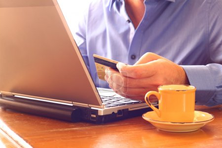 man hand holding credit card next to laptop and cup of coffee. online shopping concept. retro style image. selective focus.