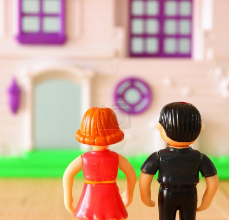 Concept image of young couple in front of new house. little plastic toy dolls (male and female) , selective focus