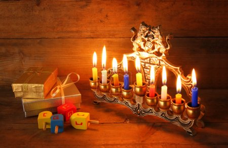 Low key image of jewish holiday Hanukkah with menorah (traditional Candelabra), donuts and wooden dreidels (spinning top).