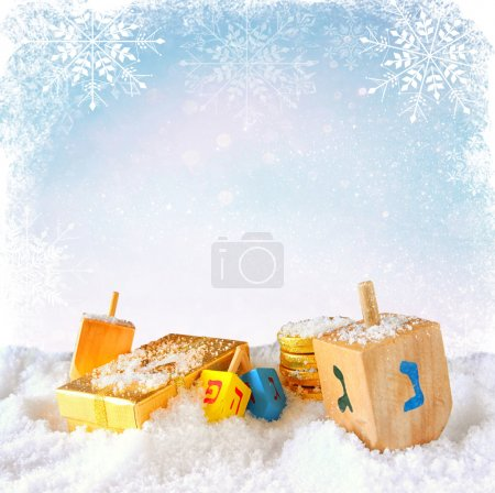 image of jewish holiday Hanukkah with wooden colorful dreidels (spinning top)  over december snow with glitter and snowflake background.
