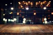 """Постер, картина, фотообои """"изображение деревянный стол перед абстрактный размытым фон огни ресторана."""""""