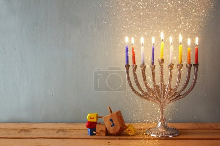 low key image of jewish holiday Hanukkah with menorah (traditional Candelabra) and wooden dreidels (spinning top). glitter background.