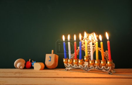 Low key image of jewish holiday Hanukkah with menorah (traditional Candelabra) and wooden dreidels spinning top over chalkboard background, room for text.