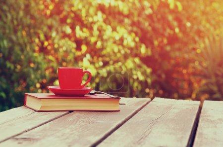 Photo pour Tasse à café tasse et réserver sur une table en bois à l'extérieur, à l'heure de l'après-midi. focus sélectif . - image libre de droit