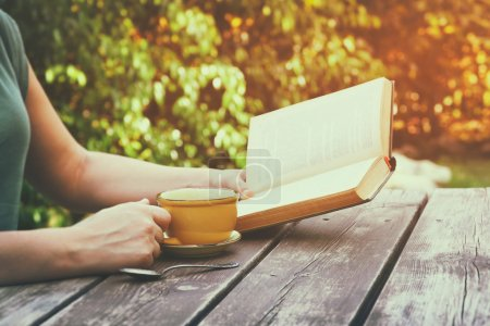 Photo for Close up image of woman reading book outdoors, next to wooden table and coffe cup at afternoon. filtered image. filtered image. selective focus. - Royalty Free Image